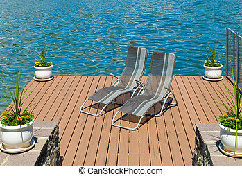 lounge chairs - pair of lounge chairs on a wooden pier in...