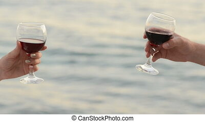 pair of lovers clink glasses with red wine on the background of the sea