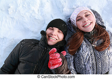 Pair of lovers people lies on snow hold on hands and laugh