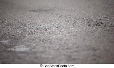 Pair of man legs run in jogging shoes on wet asphalt