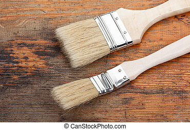 Pair of new paint brush on old wooden board construction concept.