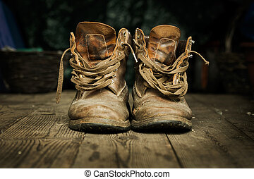 Pair of old boots on wooden floor boards - Pair of old worn ...