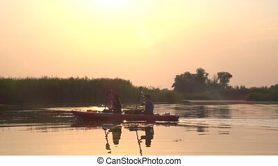 Pair of people in kayaks floats on a calm river in a sunset...