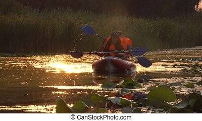 Pair of people in kayaks floats on a river in a sunset