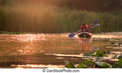 Pair of people in kayaks floats on a river in a sunset. Slow motion