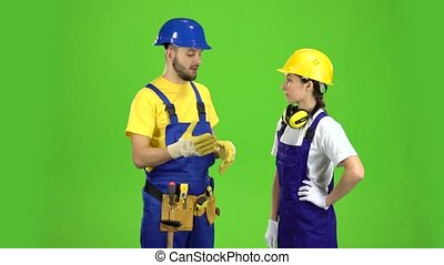 Pair of professional builders are talking among themselves. Green screen