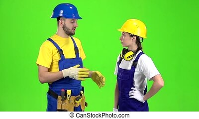 Pair of professional builders are talking among themselves. Green screen. Slow motion