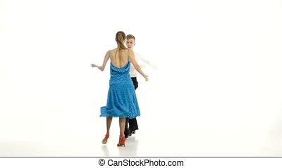 Pair of professional dancers perform rumba on white studio...