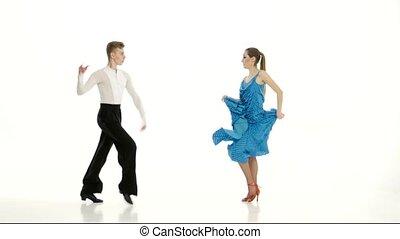 Pair of professional dancers perform salsa on white studio...