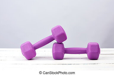 pair of purple plastic dumbbells for sports on a white wooden background