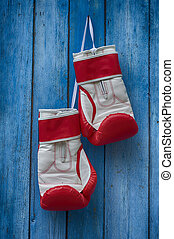 pair of red boxing gloves hanging on a nail