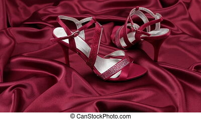 Pair of red female sandals on red cloth. Slider shot. Women'...