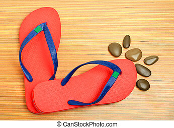 red flip-flops and pebbles on the wooden background