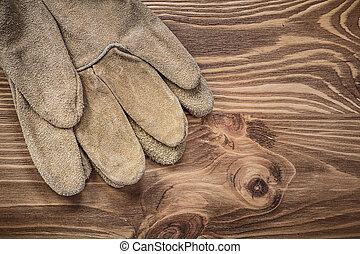 Pair of safety gloves on vintage wooden board construction conce