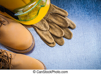Pair of safety lace boots leather gloves hard hat and transparen