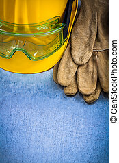 Pair of safety leather gloves hard hat and protective goggles on