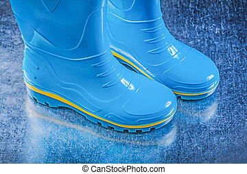 Pair of safety rubber boots on metallic background gardening concept.