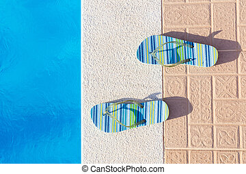Pair of slippers at edge of swimming pool