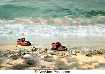 Pair of small sandals lost at the beach