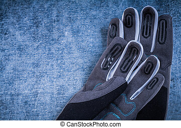 Pair of staff gardening gloves on scratched metallic background