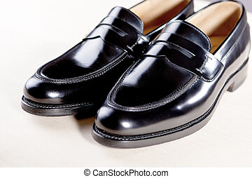 Pair of Stylish Expensive Modern Leather Black Penny Loafers Shoes.Closeup Shot.