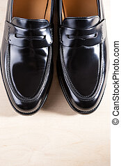 Pair of Stylish Expensive Modern Leather Black Penny Loafers Shoes.Closeup Shot