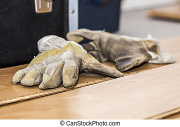 Pair of used gloves lying on removed laminate
