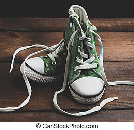 pair of very worn green textile shoes