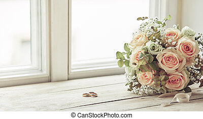 Pair of wedding rings and bridal bouquet