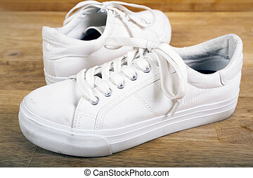Pair of white sneakers with laces
