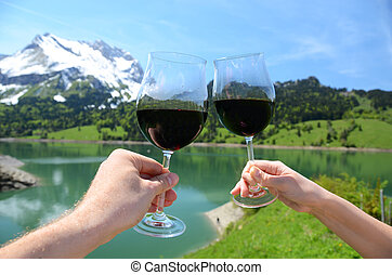 Pair of wineglasses in the hands against Alpine scenery. Switzerland