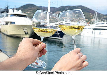 Pair of wineglasses in the hands against the yacht pier of...