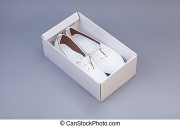 Pair of womans white shoes in box isolated on gray background