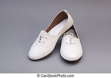 Pair of womans white shoes isolated on gray background