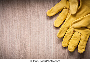 Pair of yellow leather safety gloves on wooden board copy space image gardening concept.