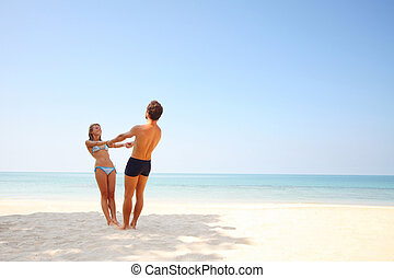 Pair - Young lovers standing on warm sand at sunny day and...