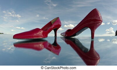 pair red woman shoe stilettos on mirror in space and clouds motion. Fashion concept. Timelapse 4K