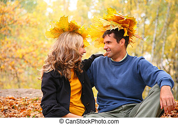 Pair with maple leaves looking each other in autumn wood