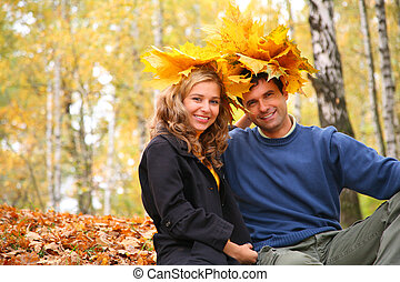Pair with maple leaves on head in autumn wood