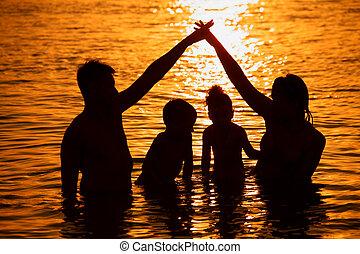pais, com, crianças, em, mar, ligado, pôr do sol