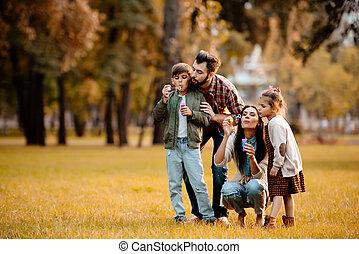 pais, com, crianças, soprar borbulha