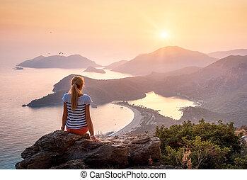 paisaje, con, niña, mar, montañas, y, cielo anaranjado