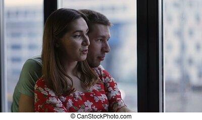 paisible, jeune couple, regarder travers, les, fenêtre