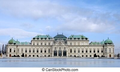 Palace Belvedere stands against blue sky in front of pond,...