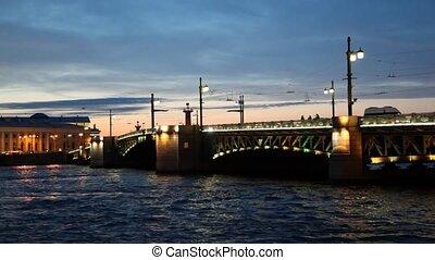 Palace Bridge on stone piers standing on Neva in evening