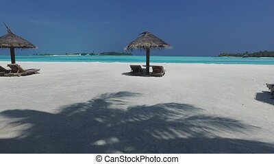 palapa and sunbeds by sea on maldives beach - travel,...