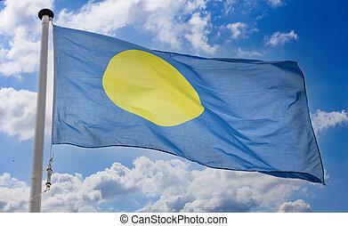 Palau flag waving against blue cloudy sky