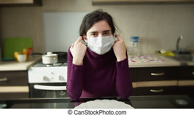 Pale sick girl sitting at home wearing a medical mask, taking it off, self-isolation
