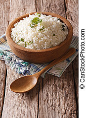Paleo Food: Cauliflower rice with herbs close-up. Vertical -...