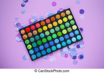 Palette of multicolored eyeshadow on pink background with colorful confetti.